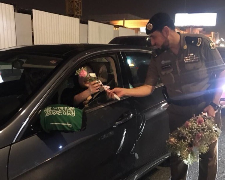 Police handing out flowers to female drivers