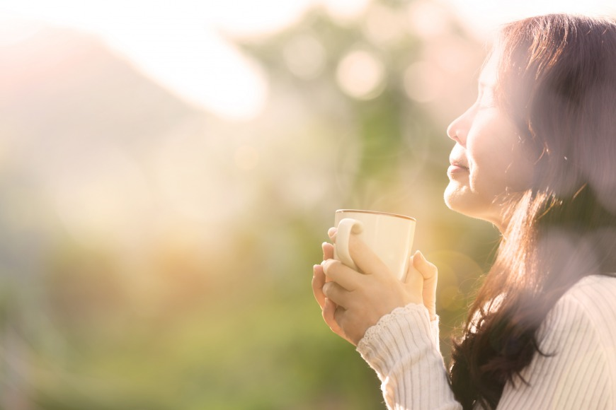 Woman feeling blissful with hands holding coffee cup