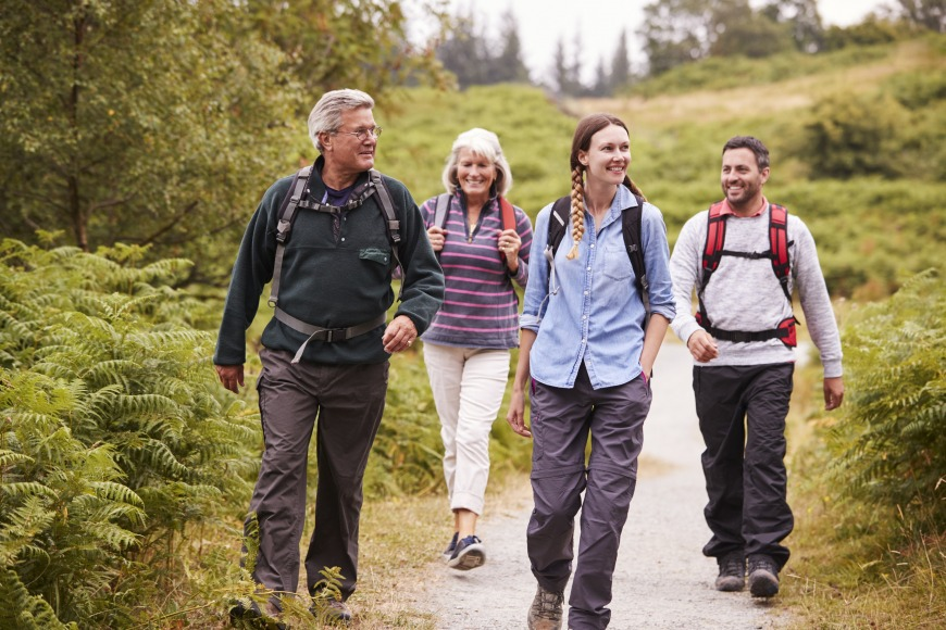 Two mixed age couples walking on a countryside path during family camping adventure, front view